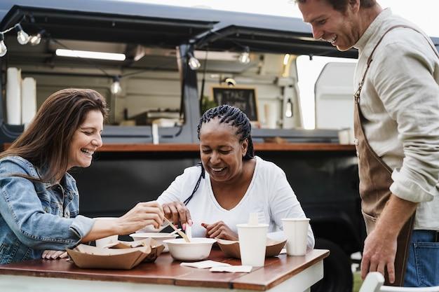 Mujeres multirraciales comiendo en el restaurante de camiones de comida al aire libre - centrarse en la cara de la mujer africana