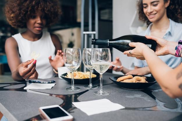 Mujeres multirraciales jóvenes sentadas en un restaurante moderno y bebiendo juntas