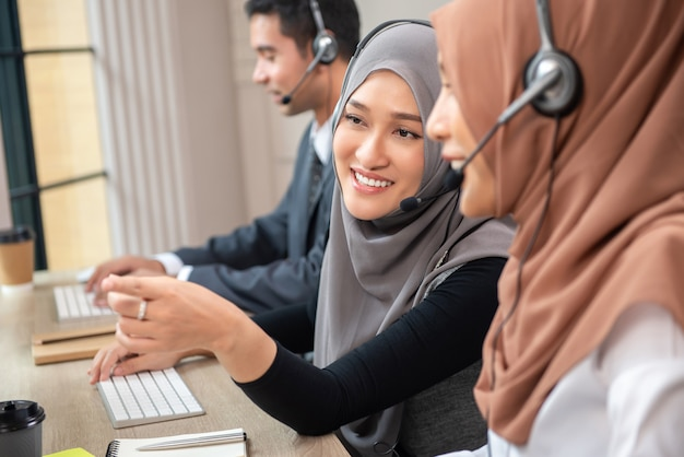 Mujeres musulmanas asiáticas hermosas felices que trabajan en la oficina del centro de atención telefónica