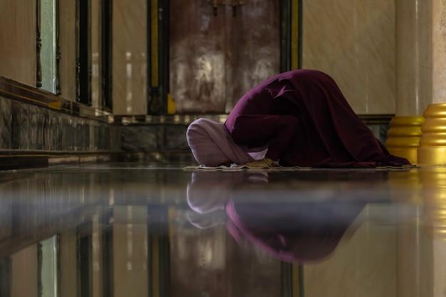 Mujeres musulmanas con camisas moradas haciendo oración del islam.