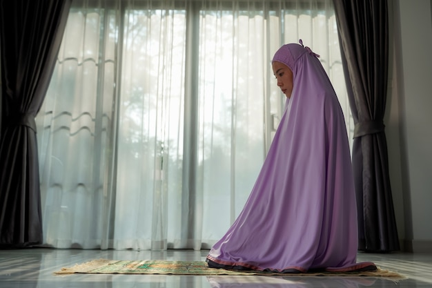 Mujeres musulmanas rezando en el vestíbulo de la casa durante el brote de coronavirus covid19