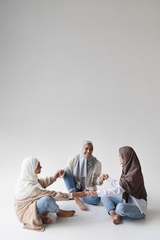 Mujeres musulmanas de tiro completo con hijabs