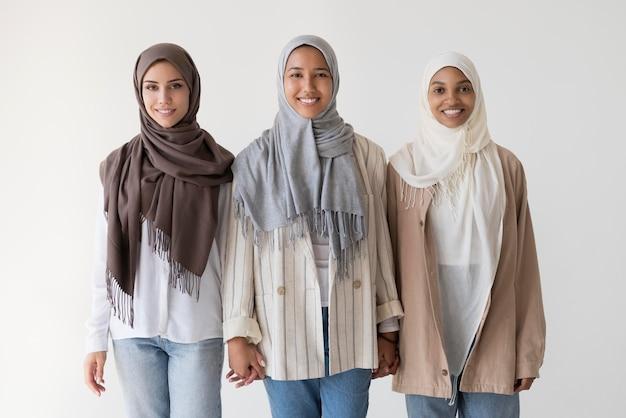 Mujeres musulmanas de tiro medio con hijabs