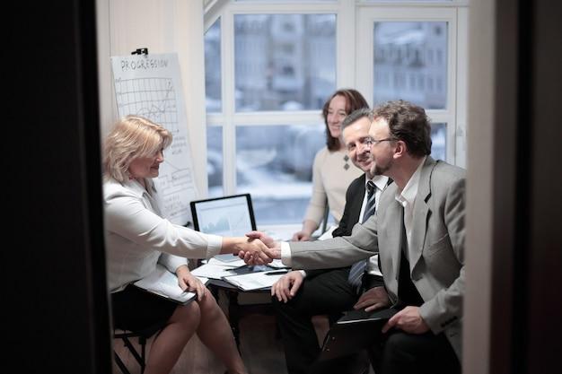 Mujeres de negocios apretón de manos con un socio sobre un escritorio en la oficina