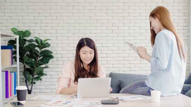 Mujeres de negocios asiáticas creativas inteligentes atractivas en la ropa de sport elegante que trabaja en el ordenador portátil mientras que se sienta