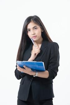 Las mujeres de negocios asiáticas están sonriendo y sosteniendo con portapapeles para trabajar feliz