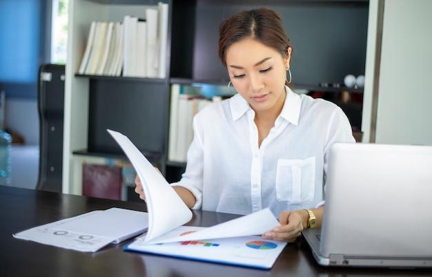 Mujeres de negocios asiáticas hermosas que comprueban el documento y que usan el cuaderno para trabajar en casa