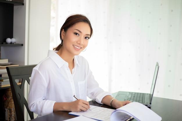 Mujeres de negocios asiáticas que usan el cuaderno y la sonrisa feliz para trabajar