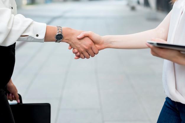 Mujeres de negocios dándose la mano en la calle