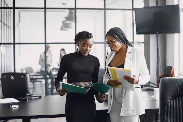 Mujeres de negocios hablando cerca del escritorio durante una pausa para el café en el pasillo de la gran corporación Foto gratis