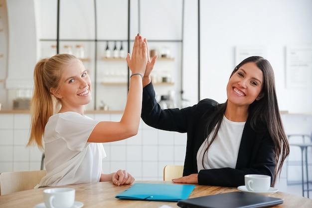 Mujeres de negocios jóvenes felices dando cinco y celebrando el éxito, sentados a la mesa con documentos y tazas de café, mirando a la cámara