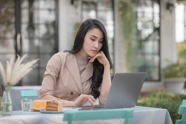 Mujeres de negocios jovenes que controlan documentos del correo en el ordenador portátil