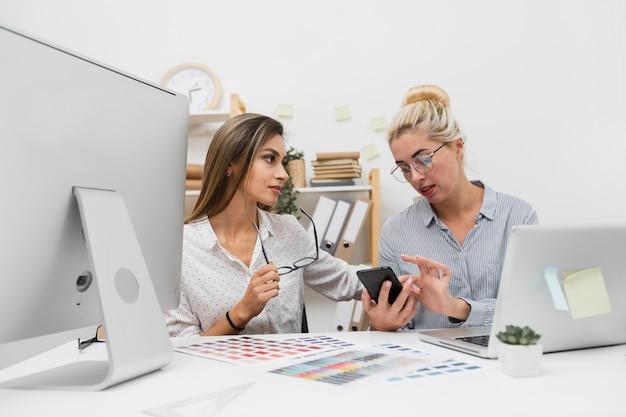 Mujeres de negocios que buscan en el teléfono