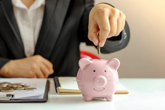Mujeres de negocios que sostienen monedas en una alcancía de cerca, incluso presionando una calculadora para ideas para ahorrar dinero.