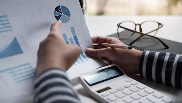 Mujeres de negocios revisando datos en cuadros y gráficos financieros