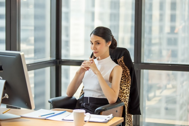 Mujeres de negocios seguros emplazamiento en oficina por ventana
