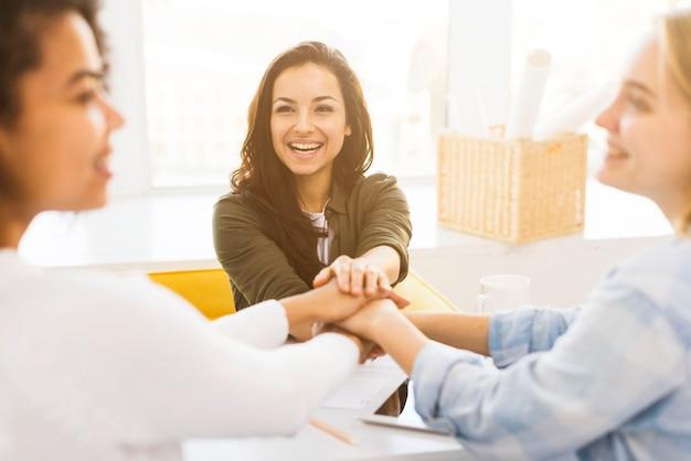 Mujeres de negocios sonrientes estrechándole la mano