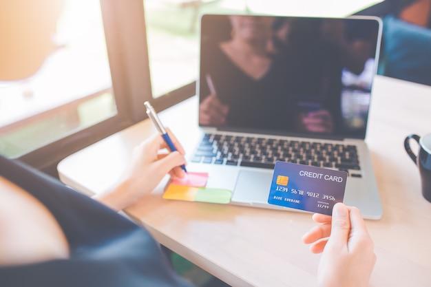 Las mujeres de negocios usan tarjetas de crédito para comprar en línea.