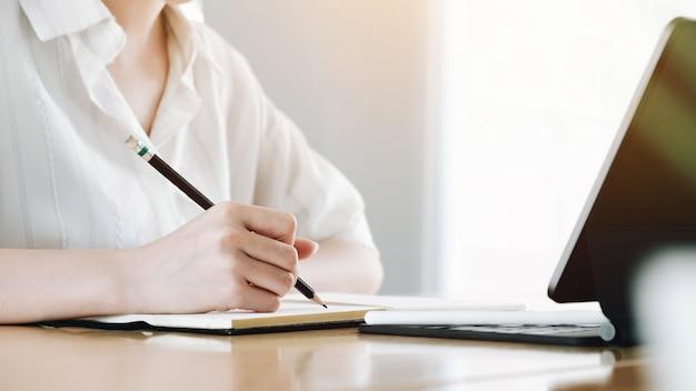 Mujeres de negocios usando laptop y anote algunos datos en el bloc de notas Foto Premium