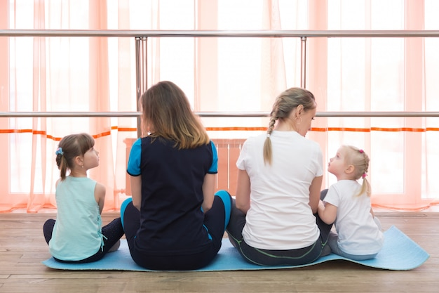 Las mujeres con niños se sientan y miran en un gran ventanal.