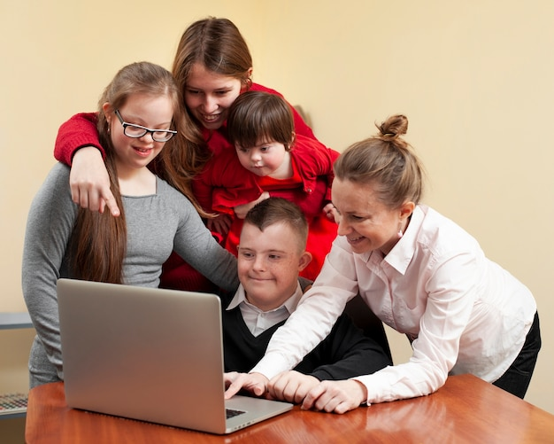 Mujeres con niños con síndrome de down en la computadora portátil