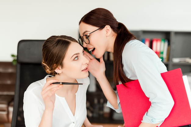 Mujeres en la oficina contando chismes