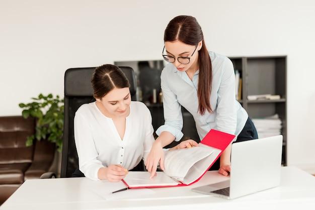 Mujeres en la oficina trabajando y firmando documentos comerciales