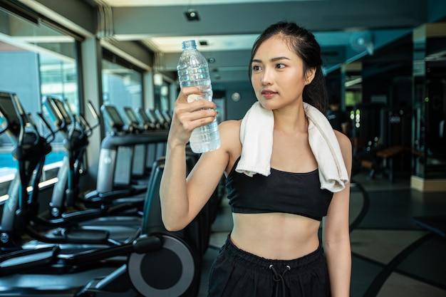 Las mujeres se paran y se relajan después de hacer ejercicio, sosteniendo y mirando la botella de agua.