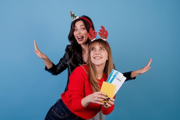 Mujeres con pasajes de avión y pasaporte vistiendo divertidos aros de navidad aislados sobre azul