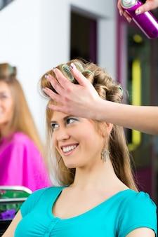 Las mujeres en la peluquería se rizó
