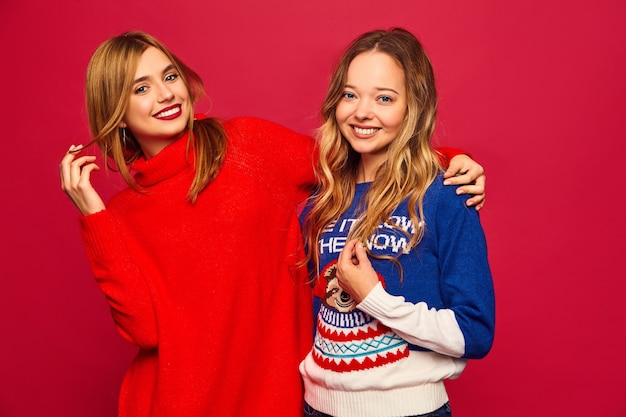 Mujeres de pie en elegantes suéteres calientes de invierno en la pared roja
