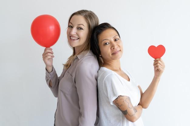 Mujeres de pie espalda con espalda con globo rojo y corazón de papel.