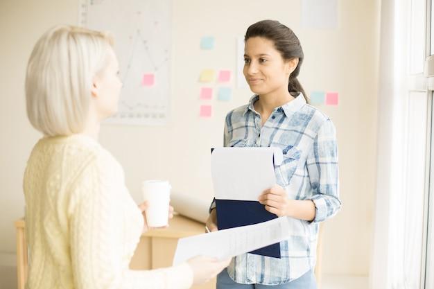Mujeres de pie en la sala de oficina hablando