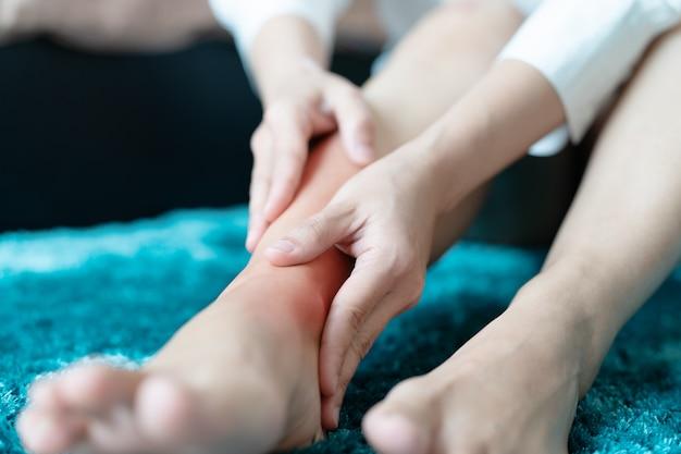 Mujeres en la pierna, lesión en el tobillo / dolor, las mujeres tocan el dolor en la pierna del tobillo