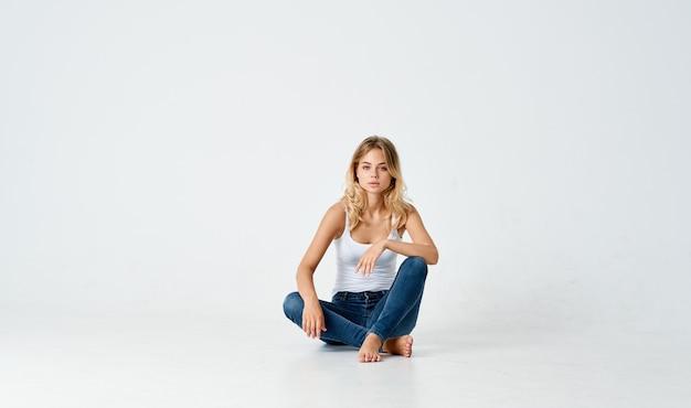 Mujeres piernas cruzadas sentadas en el suelo en el interior en jeans y camiseta