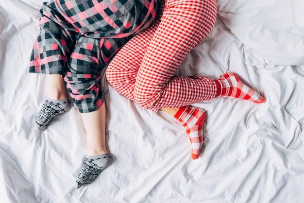 Mujeres en pijamas de colores y calcetines durmiendo en la cama.