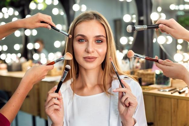 Mujeres con pinceles de maquillaje