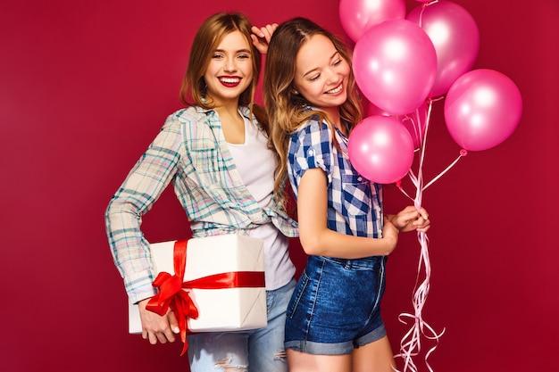 Mujeres posando con una gran caja de regalo y globos rosas
