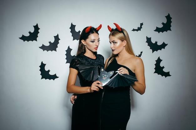 Mujeres posando con juguete de murciélago