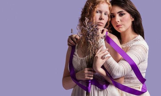 Mujeres posando con lavanda y cinta mientras se abrazan con espacio de copia