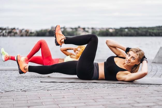Las mujeres practican ejercicios de yoga en una colchoneta en la calle cerca del agua.
