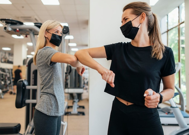 Mujeres practicando el saludo del codo en el gimnasio durante la pandemia