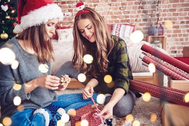 Mujeres preparando una caja de regalo mientras navidad