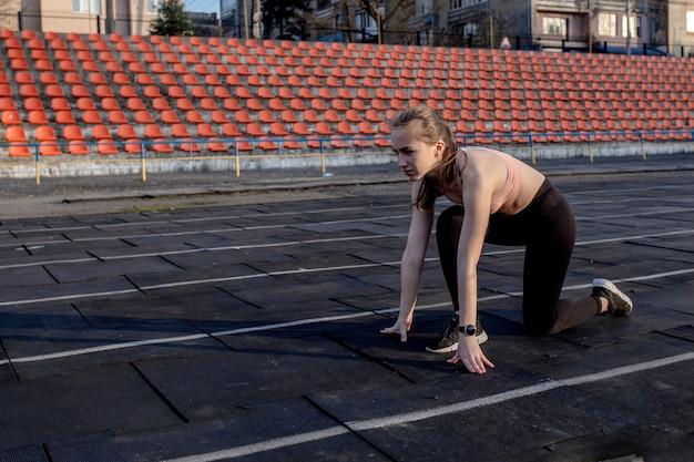 Mujeres preparándose para comenzar a correr en un estadio