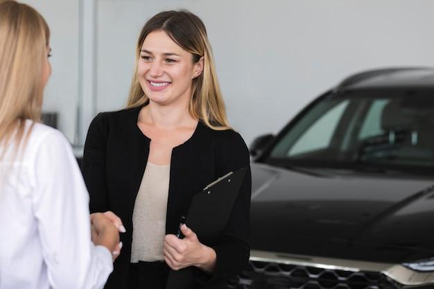 Mujeres presentándose en la sala de exposición de automóviles