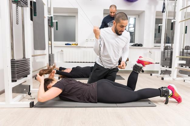 Mujeres que ejercitan las piernas con máquina de cable con entrenadores personales en el gimnasio