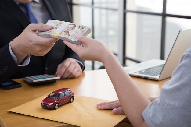 Las mujeres que envían el contrato y el documento sobre el préstamo del automóvil se presentan al banco y reciben dinero