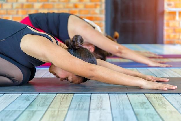 Las mujeres que hacen childs presentan en clase de yoga en gimnasio