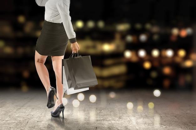 Mujeres que llevan una bolsa de compras w
