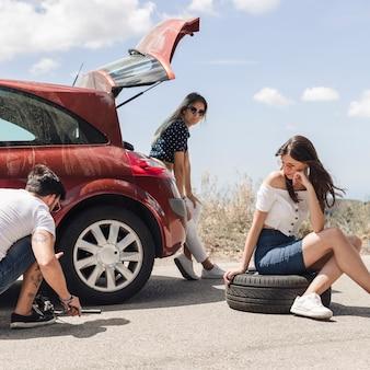 Mujeres que miran a un hombre que cambia la rueda de coche en el camino